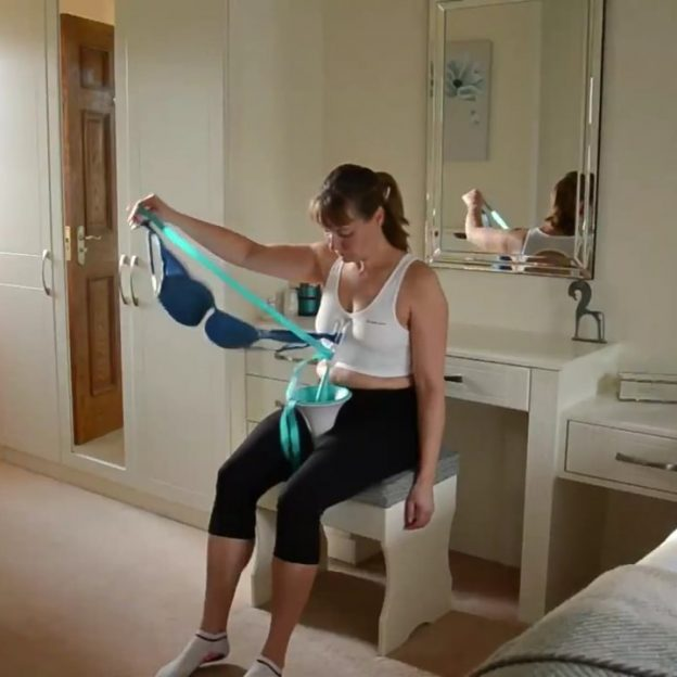 An image of a lady putting on a bra using the Bra Buddy dressing aid.