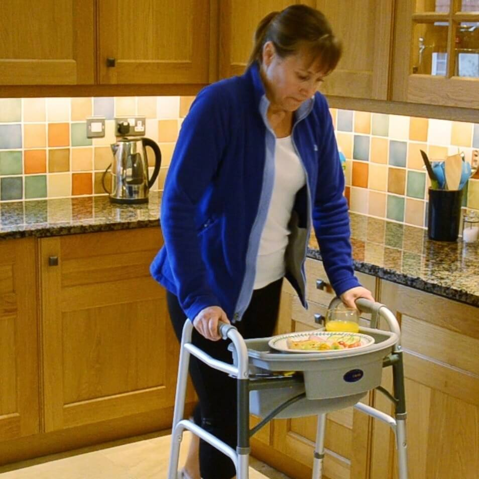 Image of a lady using the EasyCaddy with a folding walking frame in the kitchen.