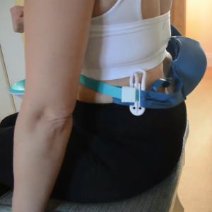 A lady tugging a bra behind her back using the BraBuddy Dressing Aid